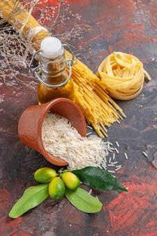 Pasta cruda vista frontale con riso e olio sulla pasta pasta cruda superficie scura