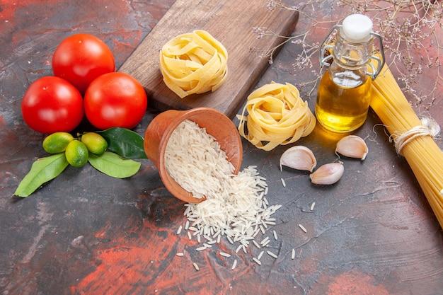 Pasta cruda vista frontale con riso e pomodori sulla pasta di pasta superficie scura cruda