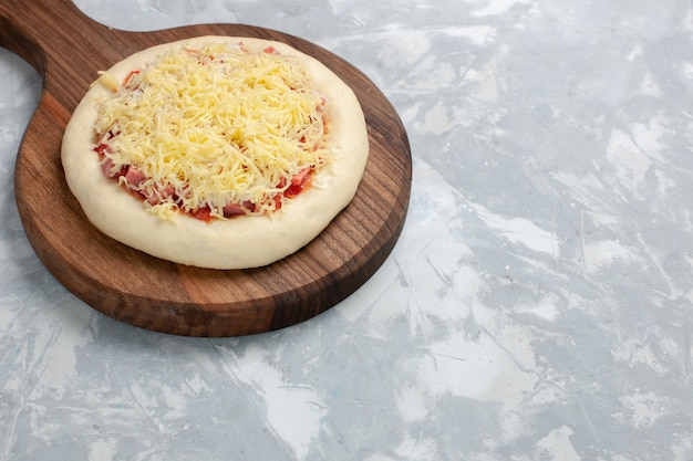 Front view raw pizza with cheese on white