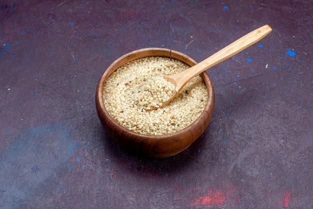 暗い背景の茶色の丸い鍋の中の正面図の生の製品