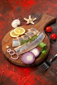 Сырая нарезанная рыба с луковыми кольцами на темном салате цвета морепродуктов, вид спереди, мясная закуска