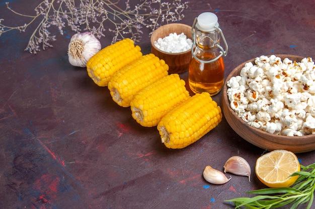 暗い表面のスナックポップコーン映画植物のトウモロコシに新鮮なポップコーンと生の黄色いトウモロコシの正面図