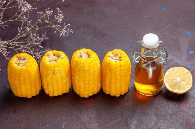 Vista frontale mais gialli crudi con olio e limone sulla pianta di film di mais popcorn snack superficie scura