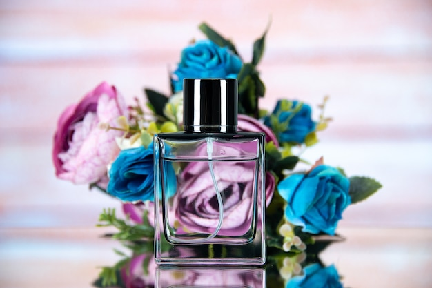 Front view of rectangle perfume bottle colored flowers on beige blurred
