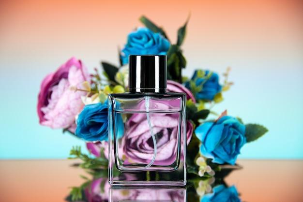 Vista frontale dei fiori colorati della bottiglia di profumo rettangolari su ombre beige