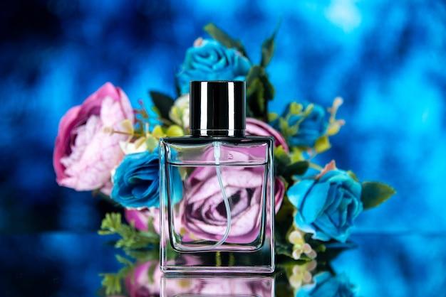Vista frontale della bottiglia di profumo rettangolare con fiori colorati su sfondo blu foto