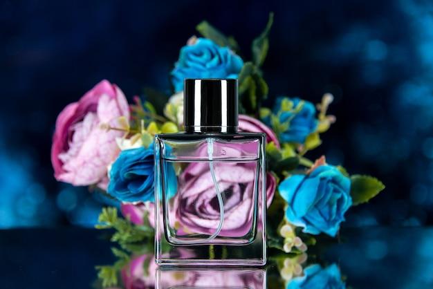 Vista frontale dei fiori colorati della bottiglia di profumo rettangolari su blu scuro