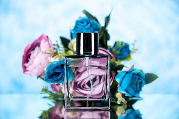 Bottiglia di profumo rettangolare vista frontale e fiori colorati su sfondo chiaro