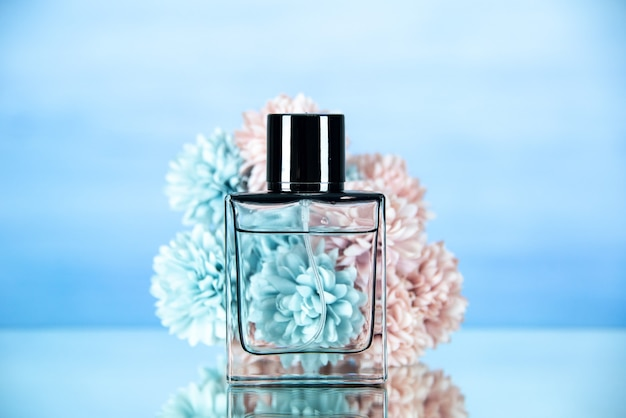 Front view of rectangle perfume bottle flowers on light blue blurred