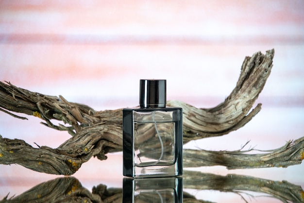 Vista frontale rettangolare bottiglia di colonia ramo legno marcio su sfondo beige