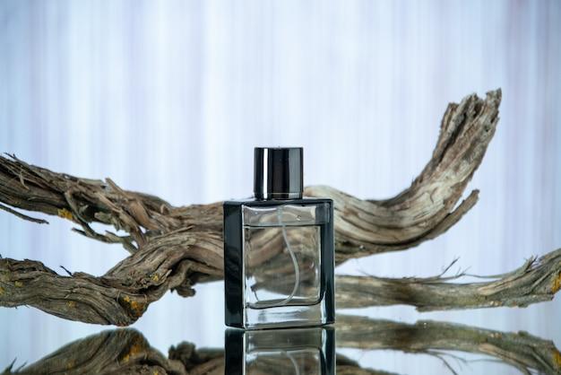 Vista frontale rettangolare bottiglia di colonia ramo legno marcio isolato su sfondo sfocato posto libero