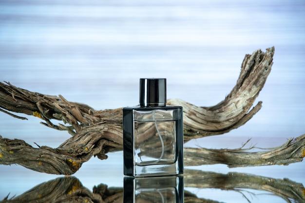 Vista frontale rettangolare bottiglia di colonia ramo legno marcio su sfondo azzurro spazio libero