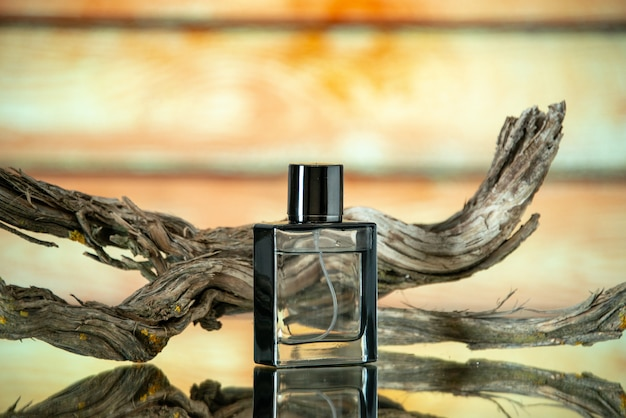 Front view rectangular cologne bottle branch rotten wood on yellow background copy place