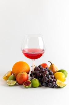 Bere alcol rosso vista frontale all'interno del vetro con diversi tipi di frutta fresca sulla barra di whisky liquore bevanda alcolica parete bianca