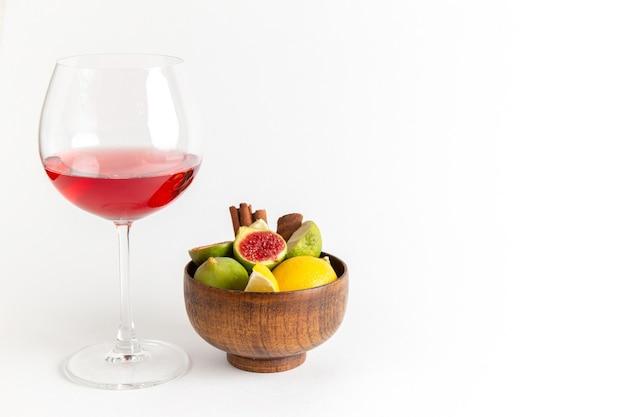 Вид спереди красный алкогольный напиток внутри стакана со свежим сладким инжиром на белом столе алкогольный напиток ликер виски-бар