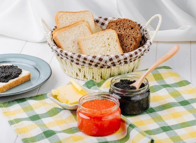 Вид спереди красной и черной икры в стеклянных банках с маслом и хлебом в корзине