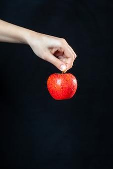 暗い表面に手に赤いリンゴの正面図