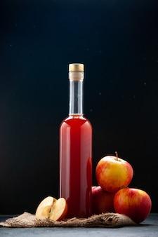 Salsa di mele rossa vista frontale in bottiglia su superficie scura