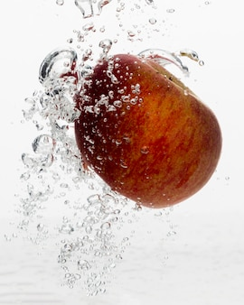 Front view of red apple in water