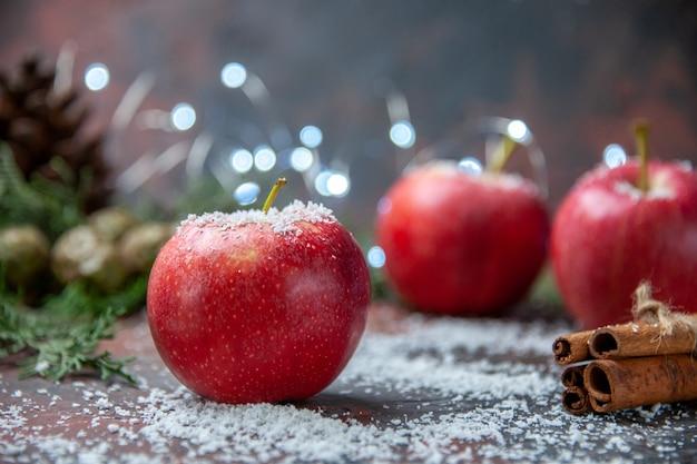 Vista frontale mele rosse bastoncini di cannella in polvere di cocco su sfondo scuro isolato