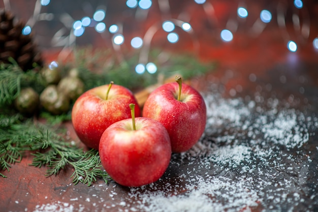 Vista frontale mele rosse bastoncini di cannella in polvere di cocco su sfondo rosso isolato