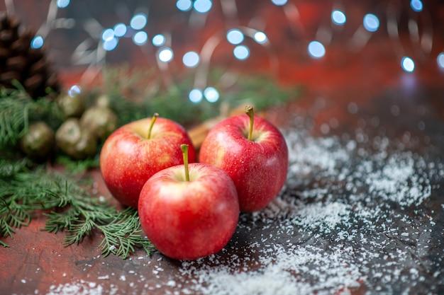 Vista frontale mele rosse bastoncini di cannella in polvere di cocco su rosso