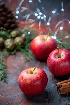 Vista frontale mele rosse bastoncini di cannella su sfondo scuro isolato
