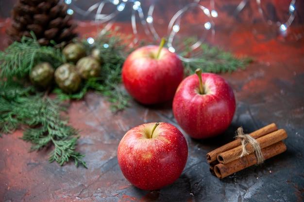 Vista frontale mele rosse bastoncini di cannella su oscurità