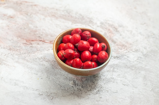 Вид спереди красные ягоды внутри тарелки на белом фоне
