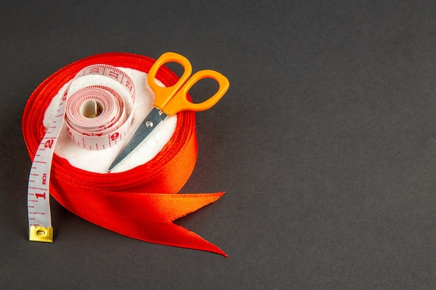 暗い背景にハサミとセンチメートルの正面図赤い弓