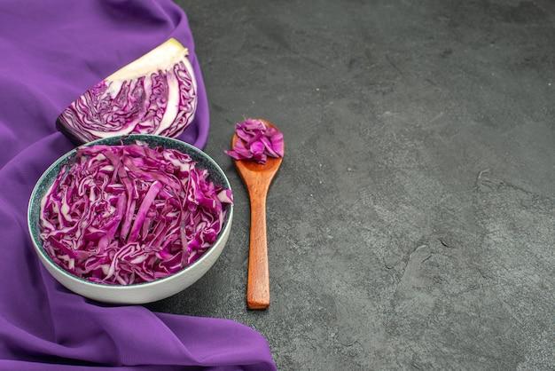 Vista frontale del cavolo rosso affettato all'interno del piatto su una dieta di insalata di tavola scura salute matura