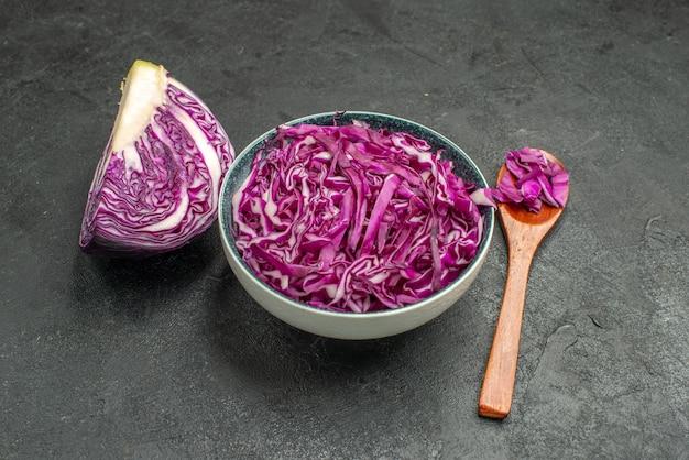 Vista frontale del cavolo rosso affettato all'interno del piatto sulla salute insalata di tavola scura matura