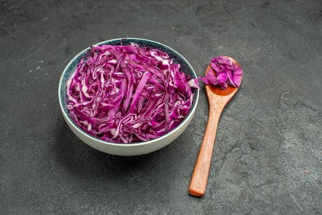 Красная капуста, нарезанная внутри тарелки, на темном столе, салат, здоровая диета, спелые, вид спереди