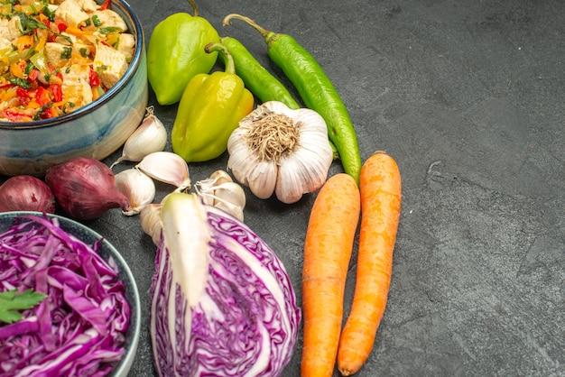 Красная капуста со свежими овощами на темно-сером столе, диетический здоровый спелый салат, вид спереди