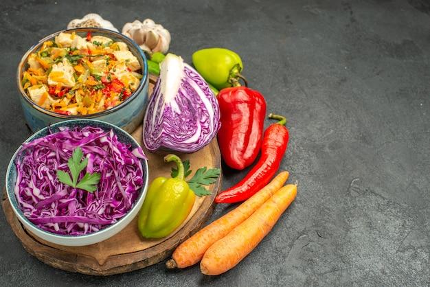 Красная капуста со свежими овощами на темно-сером столе, салат для здоровья спелой диеты, вид спереди