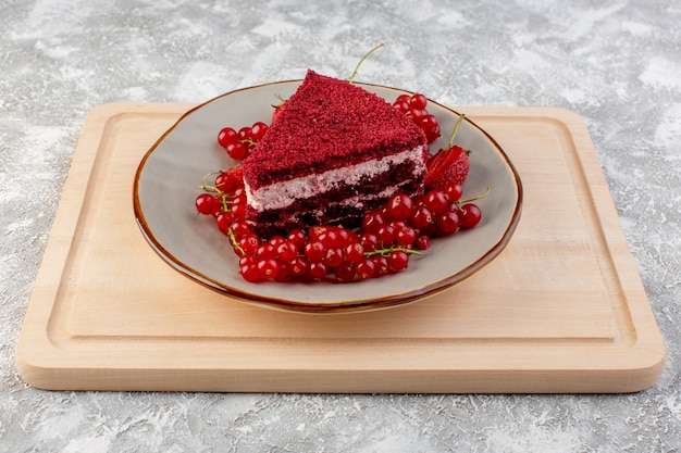 Вид спереди ломтик красного торта кусок фруктового торта внутри тарелки со свежей клюквой и клубникой на деревянном столе для чая
