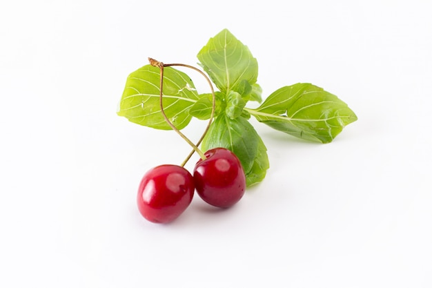 Пара красных вишен, вид спереди с зелеными листьями на белом