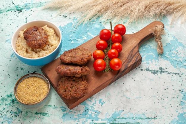 Pomodorini rossi vista frontale con cotolette di carne su farina di carne vegetale superficie blu