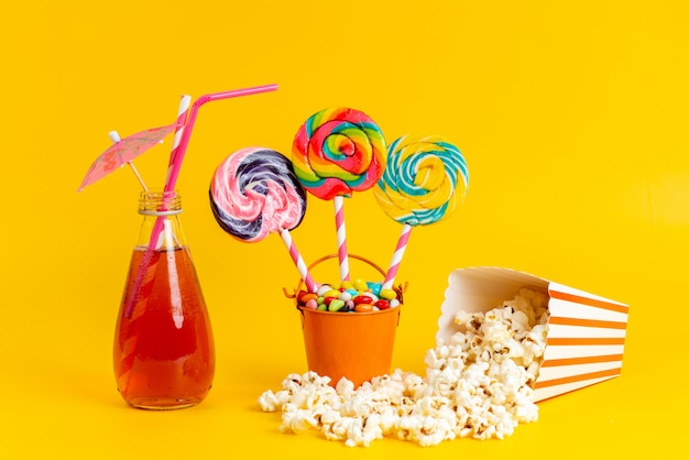 A front view red cocktail cooling with straw alogn with colorful candies lollipops and popcorn on yellow