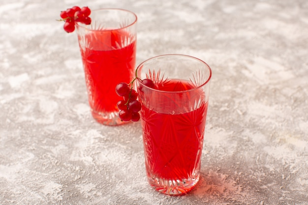 Front view red cranberry juice inside glasses on bright desk