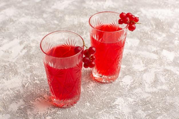 明るい机の上の長いグラスの中の正面図赤いクランベリージュース