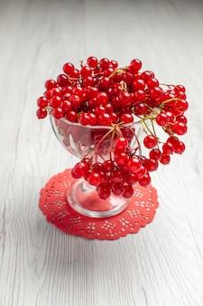 Ribes rosso di vista frontale in un vetro di cristallo sul centrino ovale rosso del pizzo sulla tavola di legno bianca con lo spazio della copia