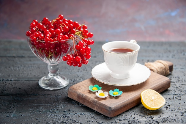 正面図赤スグリのグラスにチョッピングボードにお茶を一杯、暗い背景にレモンのスライス