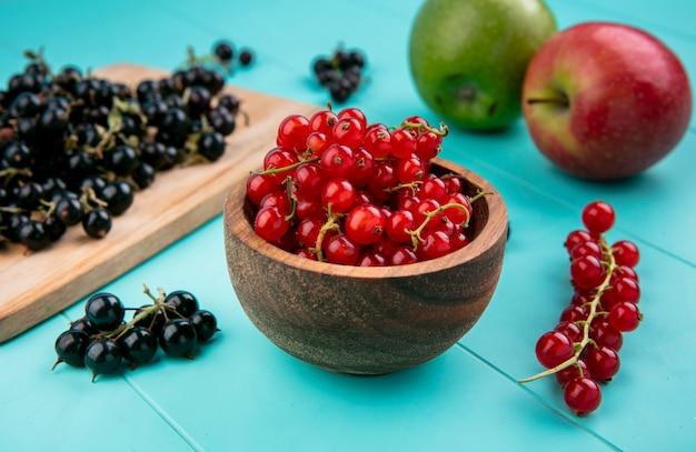 ボウルに黒スグリと明るい青の背景にリンゴのボウルに正面赤スグリ