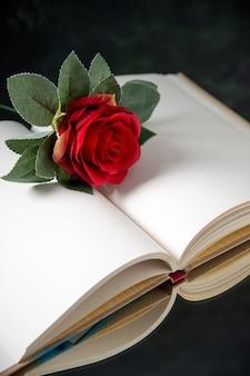 Vista frontale del fiore rosso con libro aperto su oscurità