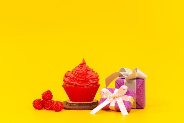 Una torta di frutta rossa vista frontale con lamponi rossi freschi e contenitori di regalo viola sullo scrittorio giallo