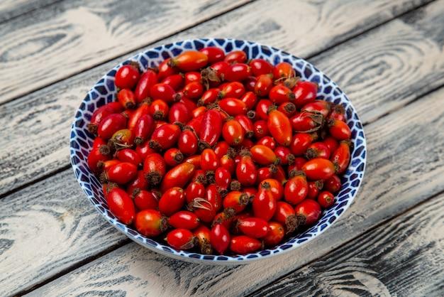 正面図灰色の机の上の赤い果実熟した酸っぱい果実果実の果実色のビタミンの木の植物