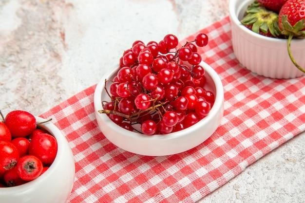 白いテーブルの上のベリーと正面図赤い果物新鮮な赤い果物ベリー