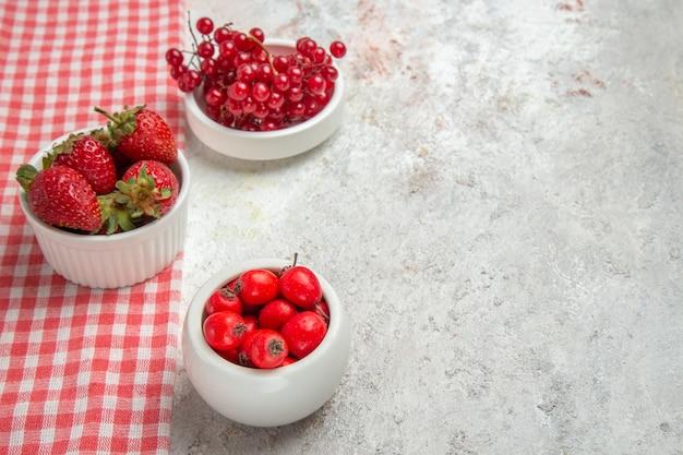 正面図白いテーブルベリーの新鮮な果物にベリーと赤い果物