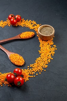 Front view of red lentils lined up in a circle and tomatoes pepper on black background